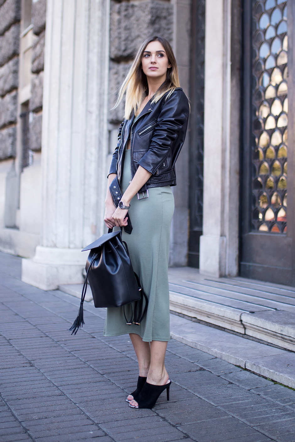 faux leather jacket over a dress in a neutral colour